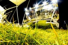 在大发光的金属盾背景的绿草  免版税库存照片