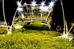 在大发光的金属盾背景的绿草  库存照片