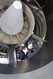 在大喷气机引擎里面的飞机机械员 图库摄影