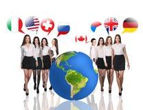 在大地球和旗子泡影附近的女商人 免版税库存图片