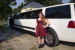 在大型高级轿车前面的美丽的青少年的女孩 库存照片