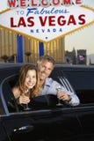 在大型高级轿车的夫妇有由欢迎的香槟槽的到拉斯维加斯标志 库存照片