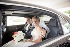 在大型高级轿车的婚礼夫妇 免版税图库摄影