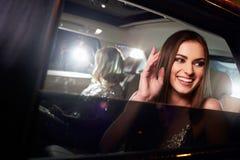 在大型高级轿车背后的两名妇女,拍摄由无固定职业的摄影师 库存图片