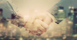 在大城市背景的商人握手两次曝光  免版税库存照片