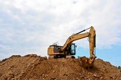 在大堆的挖掘机与蓝天的土 图库摄影