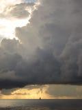 在大大厦云彩和风船后的日落 免版税库存照片