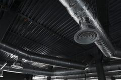 在大大厦天花板的通风系统  透气在垂悬银色的绝缘材料用管道输送从 库存图片