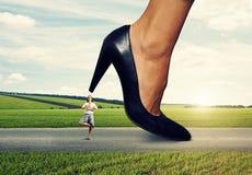在大女性脚跟下的镇静妇女 免版税库存照片