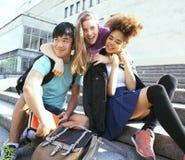 在大学大厦的逗人喜爱的小组teenages有书huggings的,回到学校 免版税库存图片