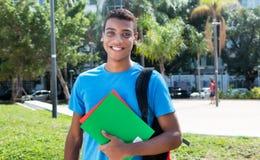在大学校园里的质朴的拉丁美洲的男学生  免版税库存图片