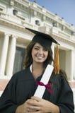 在大学画象之外的毕业生举行的文凭 库存图片
