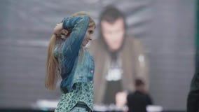 在大屏幕前面的年轻快乐的女孩爱抚头发在音乐节 股票视频