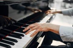 在大平台钢琴键盘的男性钢琴演奏家手 库存图片