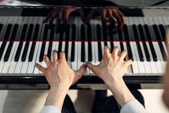 在大平台钢琴键盘的男性钢琴演奏家手 图库摄影