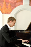 在大平台钢琴的典雅的年轻钢琴演奏家戏剧 免版税库存图片