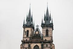 在大广场的美丽的古庙在有黑屋顶的布拉格反对灰色天空背景 库存照片