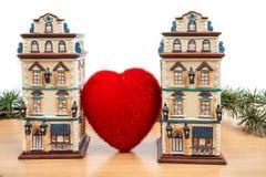 在大心脏之间的两个大厦在与白色拷贝的木桌上 库存照片