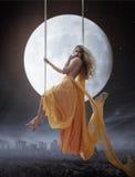 在大月亮背景的端庄的妇女 免版税库存图片
