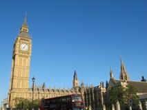 在大本钟前面的红色公共汽车在阳光,伦敦 免版税库存照片