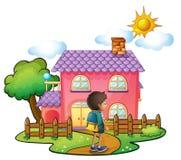 在大桃红色房子前面的一个男孩 库存图片