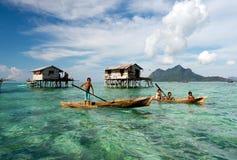 在大桶Sakaran海岸公园附近的Bajau Laut儿童明轮船 库存图片