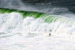 在大波浪下的冲浪者 图库摄影