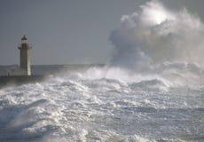 在大波浪下的灯塔 免版税图库摄影