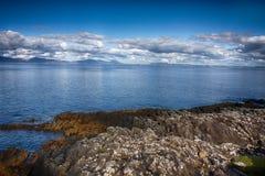 在大海和多云蓝天的岩石风景 库存照片