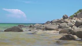 在大海海岸和wawes的大岩石  岩石岸和蓝色海水在清楚的天空风景 飞溅水的一刹那冻结的平均值移动 股票录像