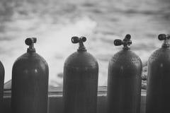 在大海背景氧气压缩空气的佩戴水肺的潜水极端体育在黑钢瓶 图库摄影