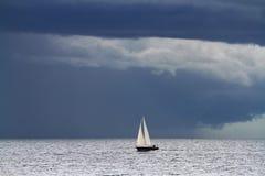 在大海洋和黑暗的云彩的小游艇 免版税库存照片
