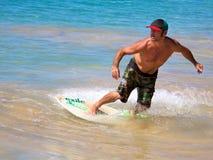 在大海滩的Skimboarding 免版税库存图片