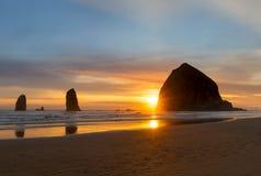 在大炮海滩的干草堆岩石在日落期间 免版税库存照片