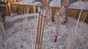 在大烟灰缸的灼烧的香火棍子在佛教寺庙 免版税图库摄影