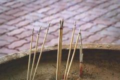 在大烟灰缸的灼烧的香火棍子 库存照片