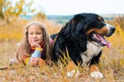 在大狗旁边的女孩谎言秋天走 免版税图库摄影