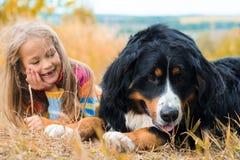 在大狗旁边的女孩谎言秋天走 免版税库存图片