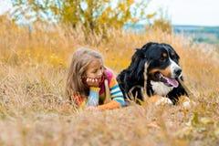 在大狗旁边的女孩谎言秋天走 免版税库存照片