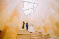 在大理石台阶的浪漫婚礼夫妇有在背景的砂岩墙壁的 低角度 库存图片