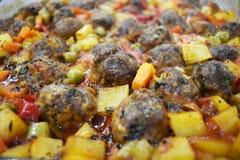 在大理石地板上,与菜的丸子,在玻璃烘烤的盘 免版税库存图片