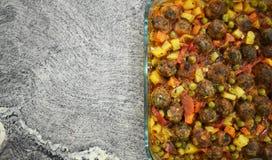 在大理石地板上,与菜的丸子,在玻璃烘烤的盘 库存照片