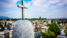 在大理石墓碑的上面的发光的金属十字架 免版税库存图片