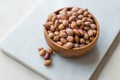 在大理石委员会的未加工的干斑豆有木碗/扁豆的 库存照片