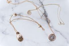 在大理石背景的金女性装饰品 免版税库存图片