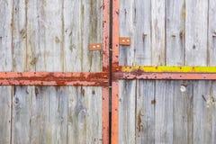在大生锈的铰链的老灰色门 免版税库存照片