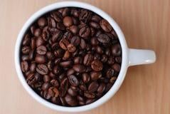 在大白色杯上射击有很多咖啡豆 免版税库存照片
