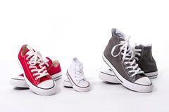 在大的父亲的鞋子,母亲媒介和儿子或者女儿小孩子大小在家庭爱概念 免版税库存图片