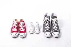 在大的父亲的鞋子,母亲媒介和儿子或者女儿小孩子大小在家庭爱概念 免版税库存照片