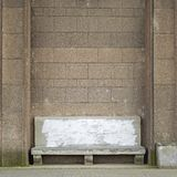在大砖墙附近的古老石长凳 库存图片